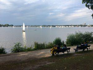 Der Blick von der Alsterwiese auf die Außenalster mit Segelbooten und Sonne